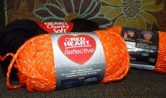 Two balls of orange reflective yarn with a ball of black yarn in the background