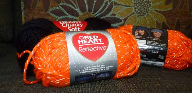 Two balls of orange Reflective yarn with a ball of Chunky soft in the background