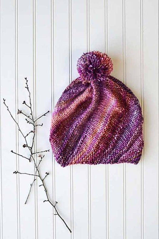Thrill Ride colorway with reds, pinks, fuschias, purples and cream is used to knit a hat with a pompom on top