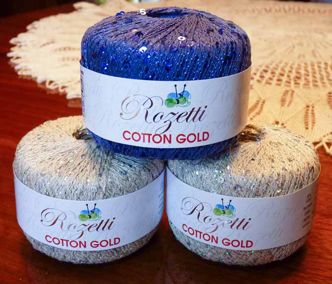 Two balls of Rozetti Cotton Gold in a soft grey with silver sequins topped with one ball in a deep blue with sapphire colored sequins
