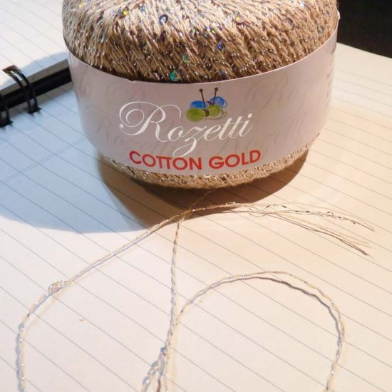 A ball of off-white Cotton Gold with a strand coiled in front. The light bouncing off the yarn produces a light ring around the base of the ball. In the foreground is a strand of the yarn showing the spacing of the sequins and the glitter strand wrapped around 3 cotton plies.
