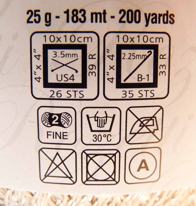 A close-up of the ball band, showing the weight and yardage, recommended needles and tension, the weight of the yarn and the laundering instructions