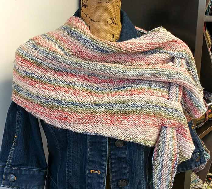 Pfeilraupe is a free pattern on Ravelry that features a point that is woven in eyelets to secure the wrap on the wearer's shoulders.
