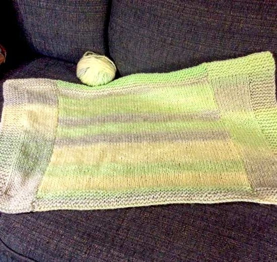 """The finished size of this prototype blanket is 26"""" [66cm] wide x 16"""" [40cm] long. If I'd had another ball of Major, I could have made it long enough to work for a baby stroller or car seat blanket."""
