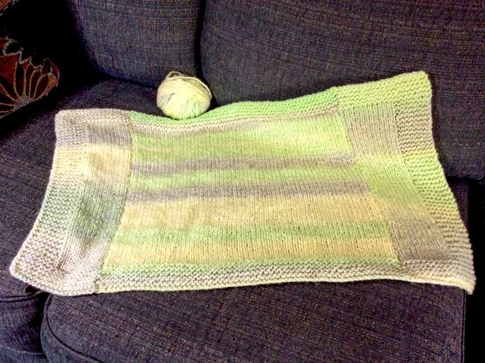 "The finished size of this prototype blanket is 26"" [66cm] wide x 16"" [40cm] long. If I'd had another ball of Major, I could have made it long enough to work for a baby stroller or car seat blanket."