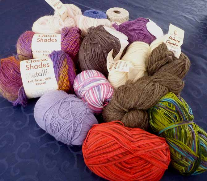 From top left: Bamboo Bloom in a soft pink colorway, Rozetti Cotton Gold in blue and off-white, a skein of Java (hemp), two skeins of Classic Chunky wool, one in white and one in pewter, Naked Sock in the Ocean colorway, Allegro in bright and deep reds, some DK that's a mystery, two skeins of Classic Shades Metallic in the Festivale colorway, and, in the middle, one ball of DK Tweed in Walnut.