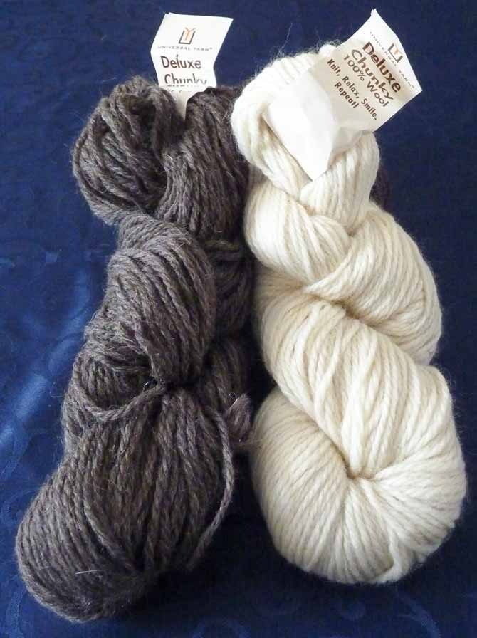 A skein each of Deluxe Chunky 100% wool yarn in off-white and grey