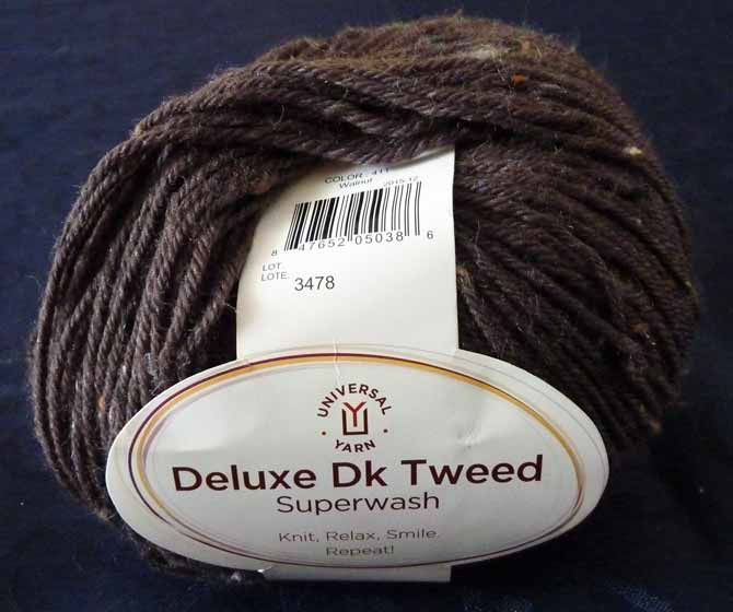 A single ball of yarn on a navy blue cloth, with the ball band. The yarn is a soft muted brown with flecks of pale orange, black, and cream. Universal Deluxe Dk Tweed Yarn
