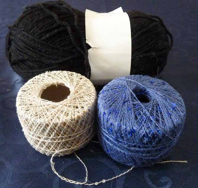A ball of black acrylic yarn in the back, with a partial ball of Rozetti Cotton Gold in blue on the right, and a scant few grams of off-white on the left.