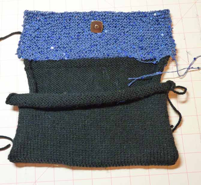 The knitted bag, with the top (blue) flap folded down and the magnetic clasp placed in the center, horizontally, and about one third down vertically.