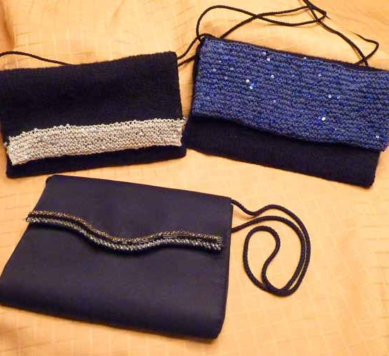 The two knitted bags, small one on the left and large, blue on on the right, propped up against a gold cloth, with a black fabric bag that has a beaded edge on the flap laying in the foreground