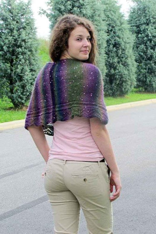 A shawlette that covers the shoulders in purple, grey, green and blue yarn with lavender sequins