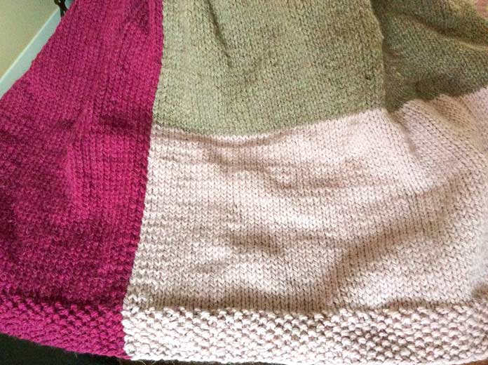 A colorway comes together! I somehow managed to reverse the blocks in my poncho, but this combination of Melanzana (left), Rosa (bottom right) and caffe (top right) is quite pretty. If you look closely, you'll see that I pretty much doubled the seed stitch border.