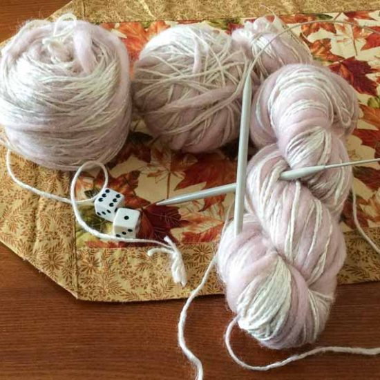 Two balls of yarn and a skein, with a grey circular needle and a pair of dice on a fall-colored, leafy table runner.