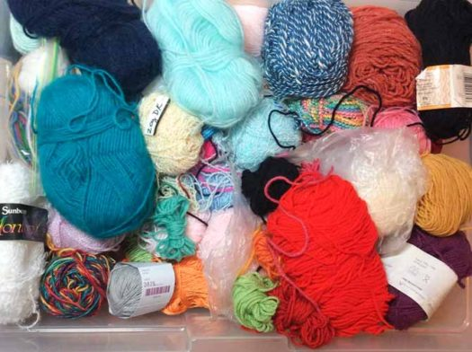 A jumble of yarn scraps in a plastic box waiting to be turned into something magical.