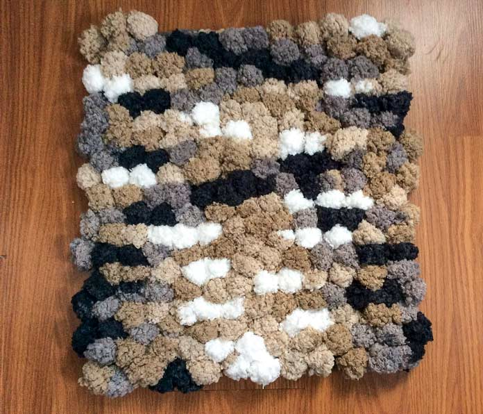"The weekend after I finished writing my posts, we bought the supplies to make a bathmat for the 'laddie.' This mat is about 18"" square and uses the Granite colorway of Pomp-a-Doodle."