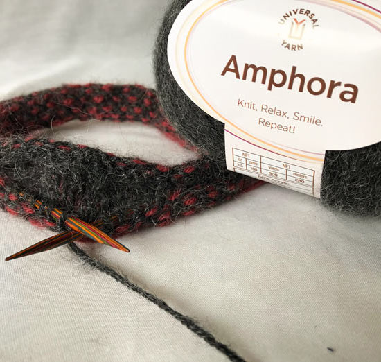 The color of Amphora yarn pictured here with wood needles is called Ebony.