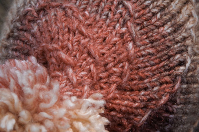 Close up of top of beanie or toque hat showing a spiraled motif and a pompom in Major by Universal Yarn