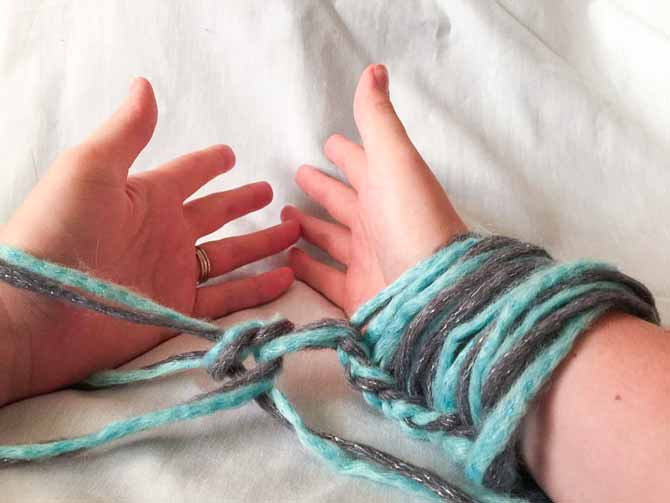 Basically you're handcuffing yourself to the yarn...but really you're arm knitting right to left.