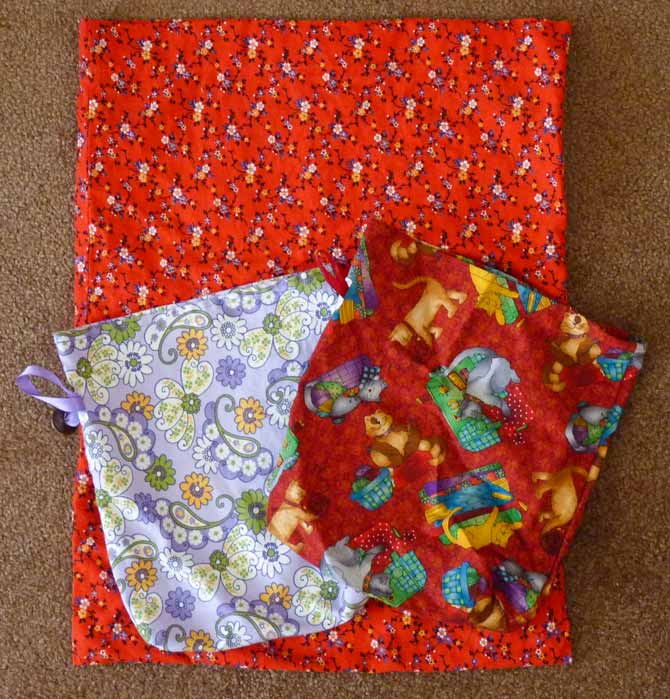 Three cloth bags laid out on a carpet. The large one, under two smaller ones, is made of red calico cotton. The small bag on top (left) is a pretty lavender paisley with shots of gold and white, while the small bag on the riight is red with cartoon cat print on it.