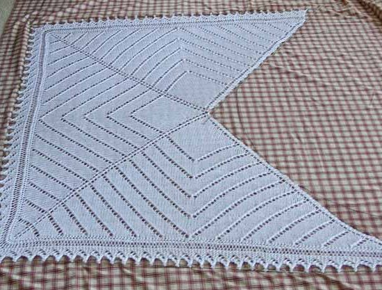 This is a wedding shawl I made in 2007 for a bride who was having a destination wedding, blocked out on a sheet and pinned to the broadloom below it. There's a blue crystal heart bead on each tip of the shawl.
