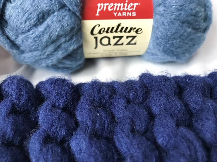 A ball of Denim colored Couture Jazz next to Navy Blue knit in a garter stitch