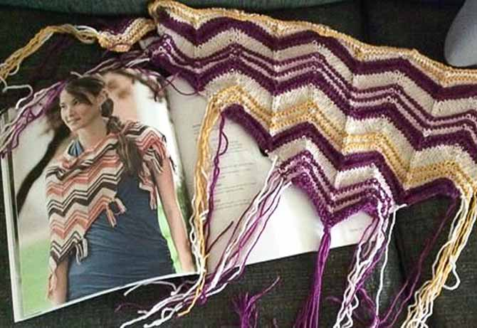 A photo of a ripple shawl with oatmeal, orange, and brown with a sample made in oatmeal, purple, and thin gold stripes beside it
