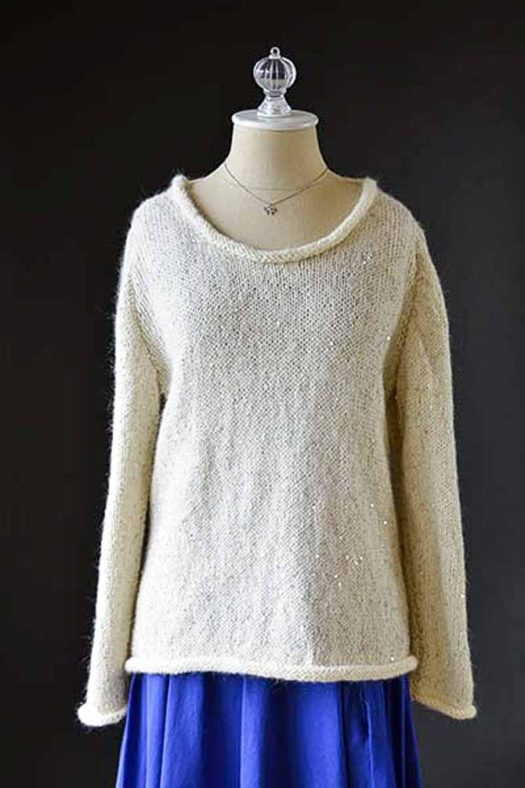 A cream colored sweater with gold sequins, long sleeves, and a scooped neck