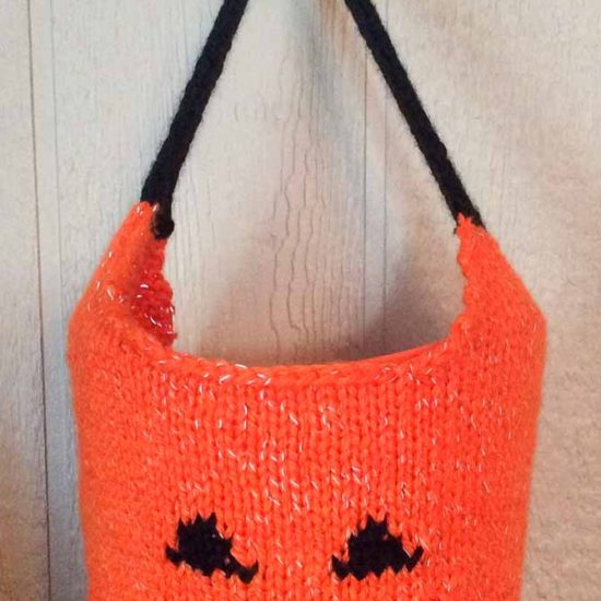 An orange knitted bag with a jack-o-lantern face and handle made in black, hanging from a hook.
