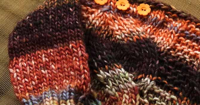Close-up of orange flower-shaped buttons on right shoulder of toddler sweater.