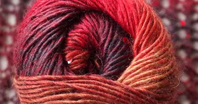 End of the skein close-up showing how mustard, pumpkin, coral pink, and merlot transition gently from one to the other in this gradient yarn.