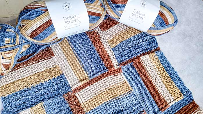 Two denim blues, taupe, camel, and chocolate brown knit up in modular blocks for a toasty warm blanket with Deluxe Stripes yarn.