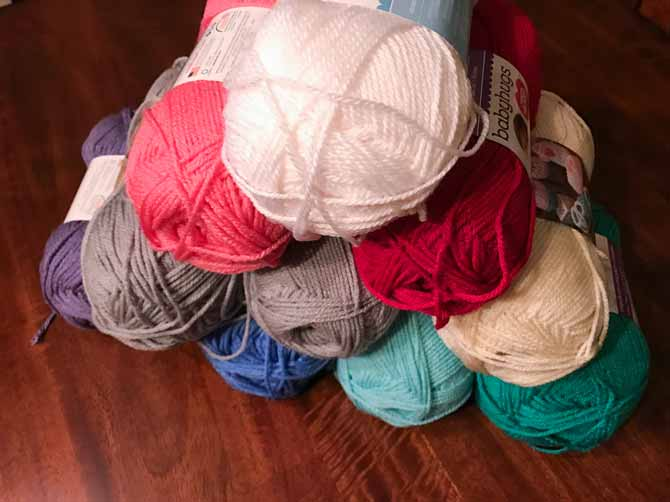 A pyramid of Red Heart's Baby Hugs Medium and Light yarn in 9 of the 18 available colors.
