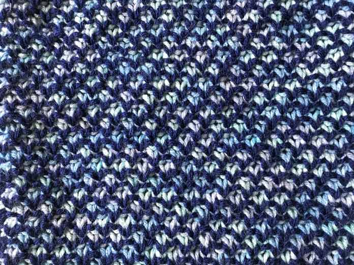 A 4 row repeat of the pattern combining a solid with a variegated creates this effect