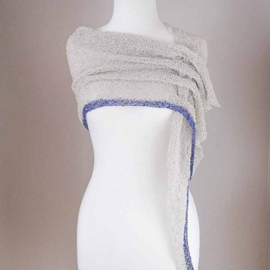 A skinny scarf in pale grey Cotton Gold with a long, thin blue stripe along one side of a very elongated triangle that has slots down the short side. The scarf is looped around the neck and the long, skinny end is threaded through the loops to create a graceful cowl.