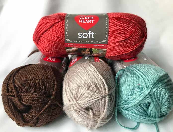 Soft yarn in the colors Cinnabar, Chocolate, Biscuit, and Sea Foam.