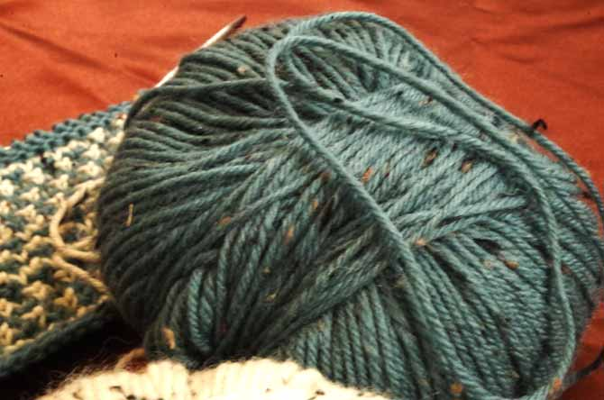 In the foregroud there are 2 balls of yarn with a swatch of slip-stitch knitting in the background.