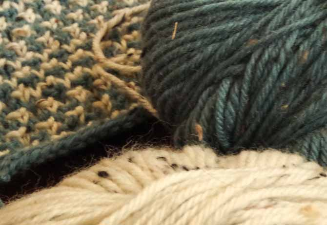 Ball of pine green tweed yarn with black, taupe and camel flecks.