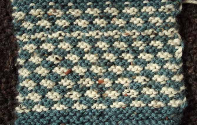 Swatch of easy-to-knit mock houndstooth pattern worked in garter stitch and slip stitches, shown in cream and pine green tweed
