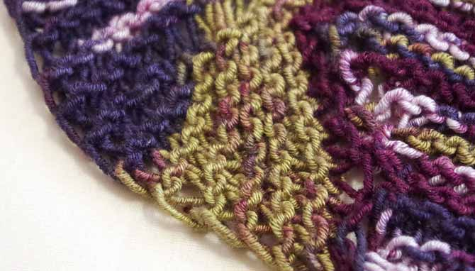 A close-up photo of one of the scallops, showing how the colors of the yarn pool in the scallops because of short rows.