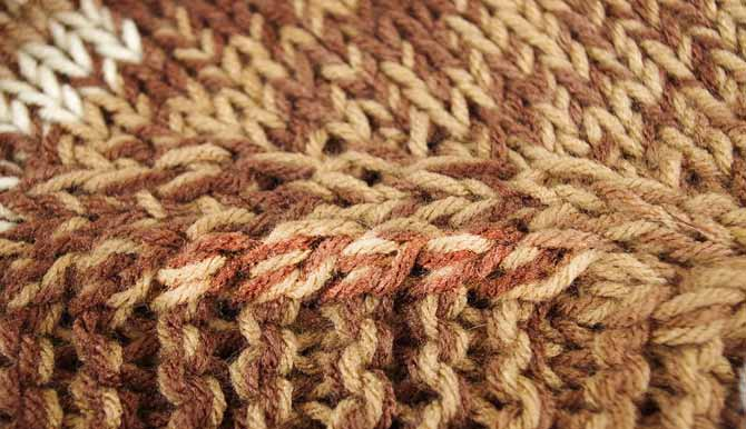 These left-leaning twisted stitches create a unique transition between stockinette and garter stitch panels.