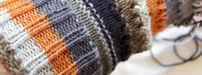 close up of cuff-down sock worked in a Prose yarn with stripes in off white, grey, medium brown-grey, charcoal and orange.