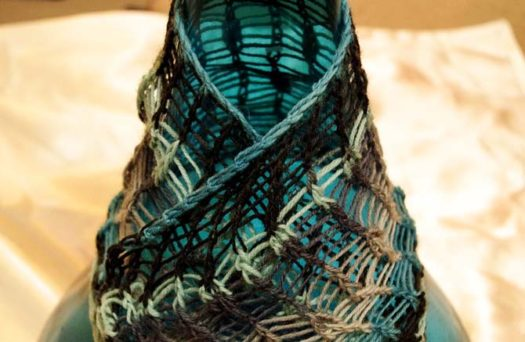 swatch of dropped stitch lace draped over a bottle. Using Prose sock yarn in 'Menswear' colorway