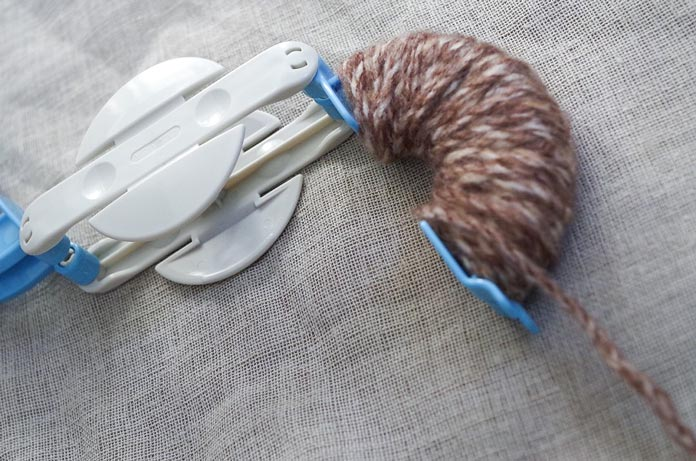 With no fuss, you wrap the yarn around the C-curve arm, ensuring that you don't go over the ends, and that you layer the same number of wraps evenly several times.