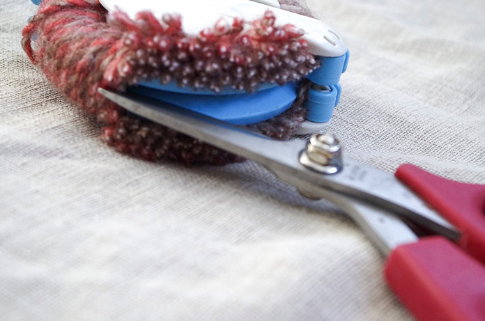 Scissors easily enter the ditch between the two halves of the Clover pompom maker to create the fuzzy ends that will become the pompom.