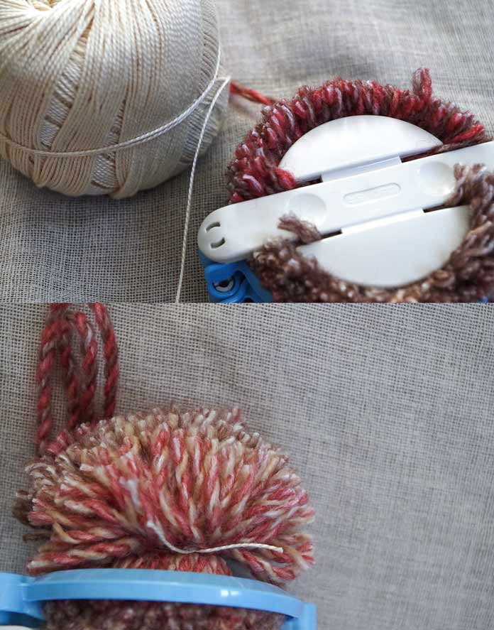 A sturdy cotton or linen string will hold the pompom together better than yarn alone.
