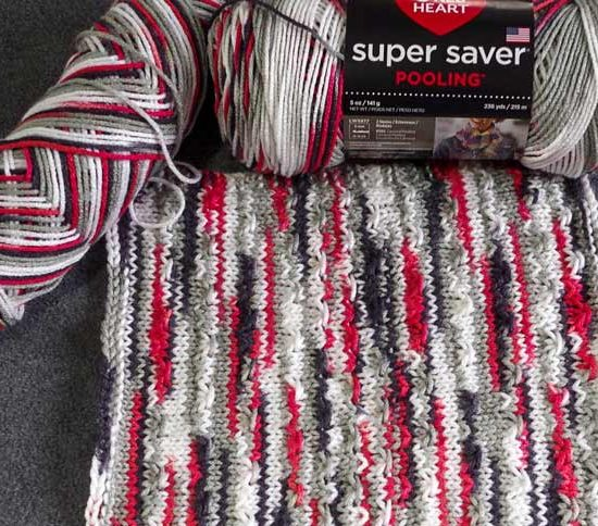 The fleck stitch pattern knit in Super Saver Pooling keeps the eye moving as it looks for a repeated color motif that isn't there.