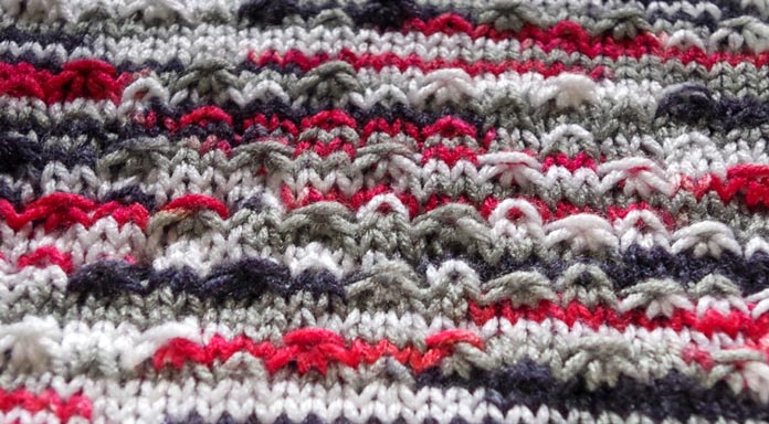 A top-down view of the fleck stitch in Red Heart Super Saver Pooling shows off the texture of this red, gray, white, and black yarn the best.