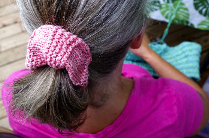 Red Heart Croquette yarn knits into a vibrant hair scrunchie