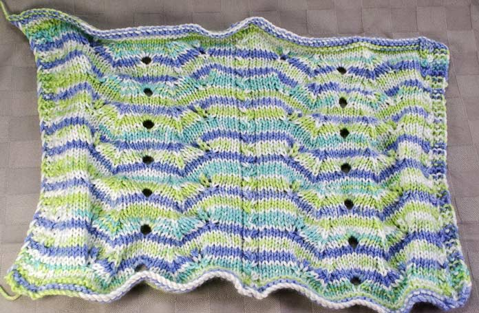 The unblocked lovey blankie is really rippling all over the place, but this acrylic yarn can indeed be blocked.